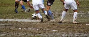 白いユニフォームで試合するサッカー選手