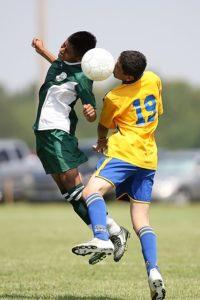 サッカーの試合、ヘディングで競いあう選手