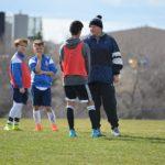選手と会話しているサッカーコーチ