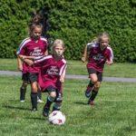 サッカーでパスを狙う少女の写真